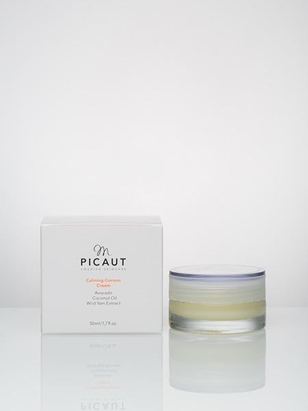 Calming Cocoon Cream från M Picaut Skincare. Ekologisk barriärkräm med avokado, kokosolja och vildjamsextrakt. 50 ml glasburk med frostat lock med vit etikett. Stilren svart logga och beskrivning, samt produktnamn i orange färg. Ekologisk vit kartong med samma färger som på burken.